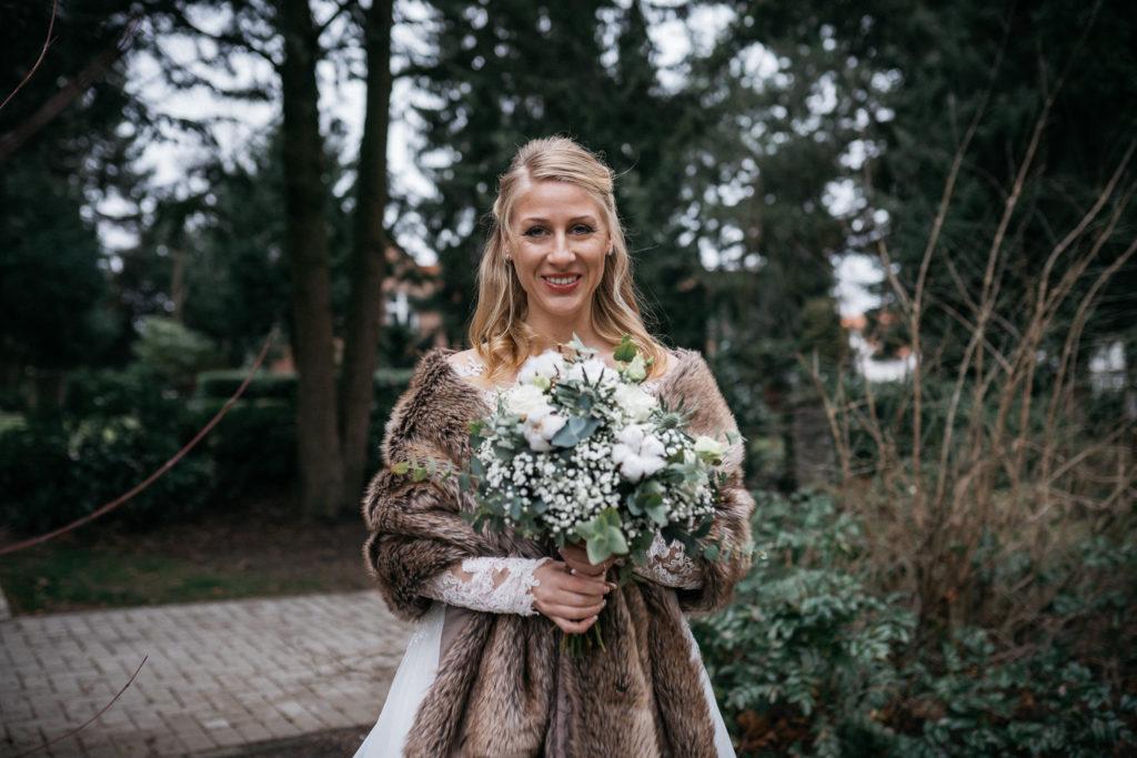 Winterbraut mit Mantel und grün-weißem Brautstrauß